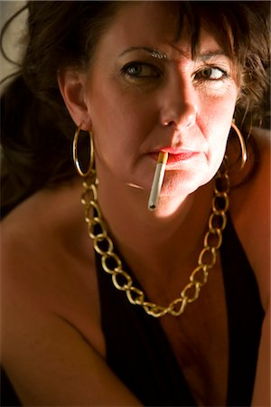 Portrait of woman in gold jewelry with cigarette in mouth Stock Photo - Rights-Managed, Code: 842-02753091