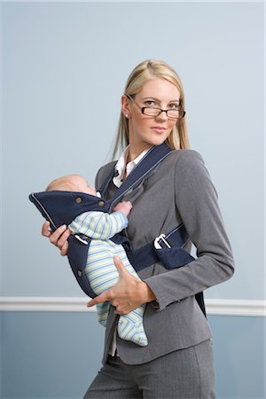 Portrait of young businesswoman holding baby at work Stock Photo - Rights-Managed, Code: 842-02753515