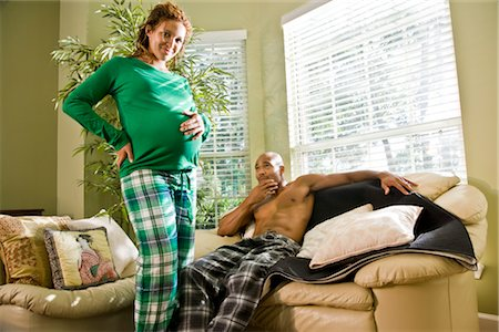 pregnant couple couch - Portrait of pregnant African American woman standing with hand on stomach, man sitting on sofa Stock Photo - Rights-Managed, Code: 842-02753685