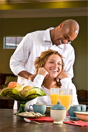 Laughing African American woman sitting at table having breakfast, man massaging shoulders Stock Photo - Rights-Managed, Code: 842-02753718