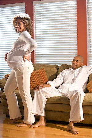 pregnant couple couch - Portrait of pregnant African American woman standing in living room, man sitting on sofa Stock Photo - Rights-Managed, Code: 842-02753758