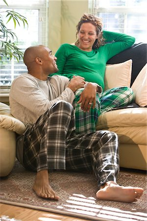 pregnant couple couch - Portrait of African American couple sitting in living room wearing pajamas Stock Photo - Rights-Managed, Code: 842-02753751