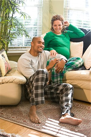 pregnant couple couch - Portrait of African American couple sitting in living room wearing pajamas Stock Photo - Rights-Managed, Code: 842-02753752