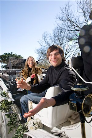 Young couple riding in horse-drawn carriage Stock Photo - Rights-Managed, Code: 842-03198852