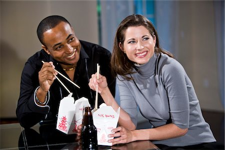Multi-ethnic couple eating Chinese take-out in modern loft Stock Photo - Rights-Managed, Code: 842-03200007