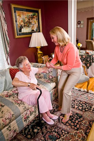 Adult daughter helping senior mother with cane in living room Stock Photo - Rights-Managed, Code: 842-03200032