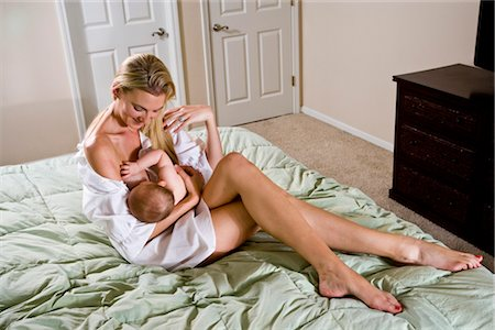 Young mother breastfeeding 6 month old baby in bedroom Stock Photo - Rights-Managed, Code: 842-03200114