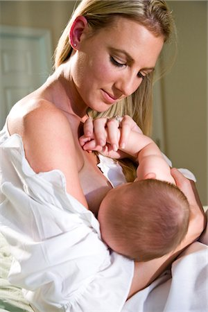 Young mother breastfeeding 6 month old baby in bedroom Stock Photo - Rights-Managed, Code: 842-03200118