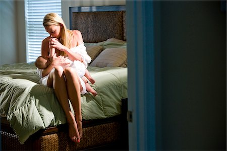 Young mother breastfeeding 6 month old baby in bedroom Stock Photo - Rights-Managed, Code: 842-03200139
