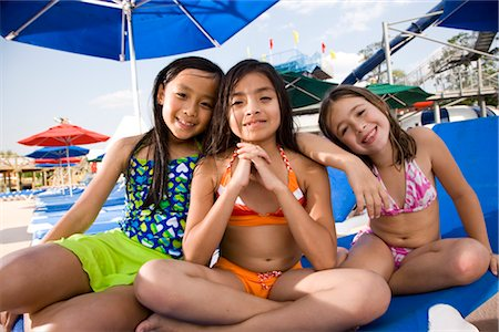 Multi-ethnic girls in swimsuits sitting on lounge chair in water park Stock Photo - Rights-Managed, Code: 842-03200238