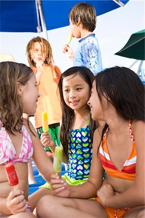 Multi-ethnic children wearing swimsuits eating popsicles Stock Photo - Rights-Managed, Code: 842-03200241
