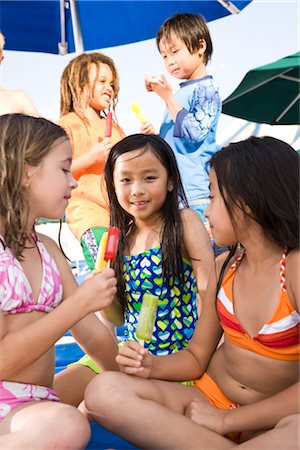 Multi-ethnic children wearing swimsuits eating popsicles Stock Photo - Rights-Managed, Code: 842-03200242