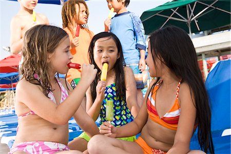 Multi-ethnic children wearing swimsuits eating popsicles Stock Photo - Rights-Managed, Code: 842-03200243