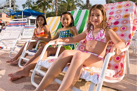 Multi-ethnic girls sitting on deck chairs at water park in summer Stock Photo - Rights-Managed, Code: 842-03200251