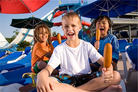 Multi-ethnic boys at water park in summer eating corn dogs Stock Photo - Rights-Managed, Code: 842-03200272