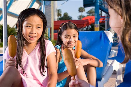Three young girls at water park eating corn dogs Stock Photo - Rights-Managed, Code: 842-03200283