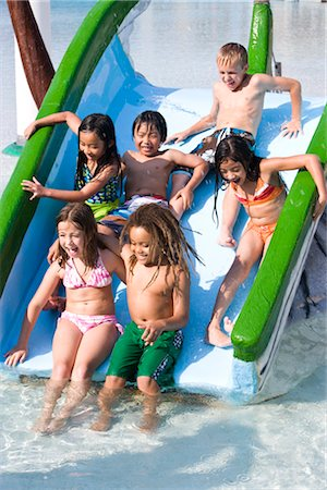 Group of children sliding down waterslide together Stock Photo - Rights-Managed, Code: 842-03200311