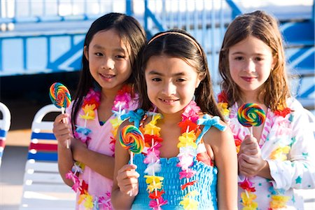 Girls with lollipops and flower leis on pool deck in summer Stock Photo - Rights-Managed, Code: 842-03200337