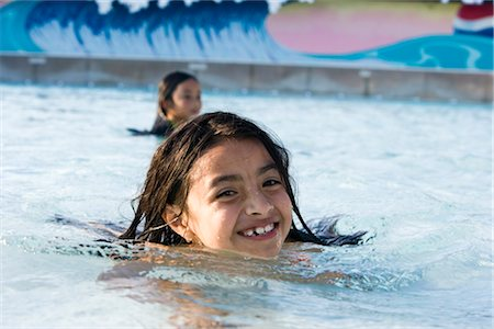 Smiling young girl swimming in wave pool at water park in summer Stock Photo - Rights-Managed, Code: 842-03200332