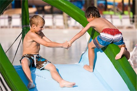 Two boys at water park in summer playing on slide near pool Stock Photo - Rights-Managed, Code: 842-03200367
