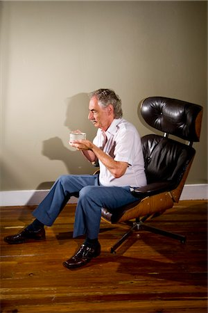 Senior man sitting in chair holding cup Stock Photo - Rights-Managed, Code: 842-03200624