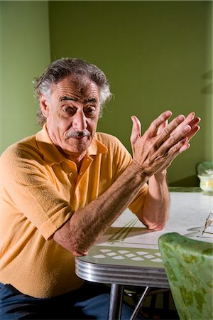 Senior man sitting at kitchen table gesturing with hands Stock Photo - Rights-Managed, Code: 842-03200635