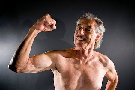 Senior man flexing muscles against gray background Stock Photo - Rights-Managed, Code: 842-03200644
