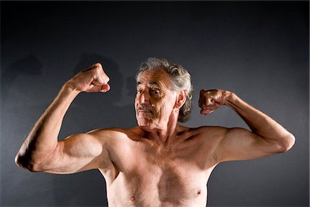 Senior man flexing muscles against gray background Stock Photo - Rights-Managed, Code: 842-03200645