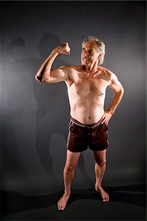 Senior man flexing muscles against gray background Stock Photo - Rights-Managed, Code: 842-03200643