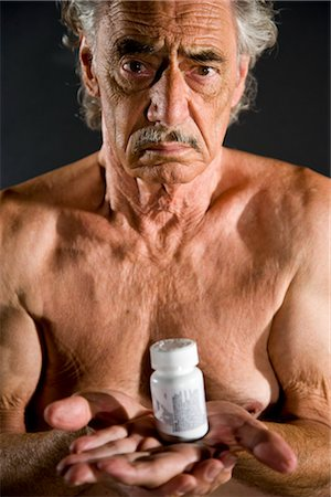 Old man holding medicine bottle, studio shot Stock Photo - Rights-Managed, Code: 842-03200664