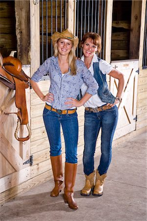 Teenage girl and mother in stable with saddle Stock Photo - Rights-Managed, Code: 842-03200693