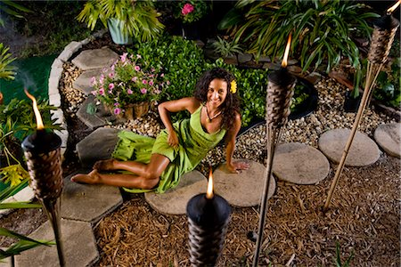 sexy women legs - Young Hispanic woman in green dress relaxing in tropical garden with tiki torches Stock Photo - Rights-Managed, Code: 842-03200802