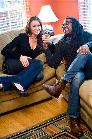 Interracial couple sitting on couch in living room Stock Photo - Rights-Managed, Code: 842-03200905
