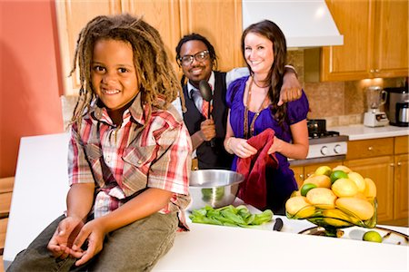 Little boy sitting on kitchen counter with interracial parents standing behind Stock Photo - Rights-Managed, Code: 842-03200901
