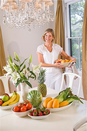 Woman in dining room with fresh fruits and vegetables on table Stock Photo - Rights-Managed, Code: 842-03200934