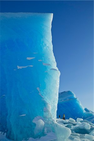A wall of blue ice towers above hikers as they explore a huge iceberg frozen into the surface of Mendenhall Lake, Mendenhall Glacier, Juneau, Southeast Alaska, Winter Stock Photo - Rights-Managed, Code: 854-05974174
