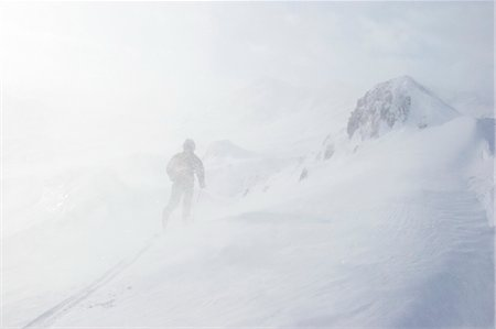 Backcountry skier skis through the Chugach Mountains near Girdwood Alaska with blowing snow and low visibility Stock Photo - Rights-Managed, Code: 854-02954912