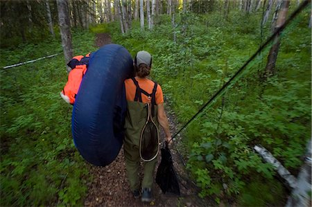 quest - Fly fisherwoman hikes her float tube into Craig Lake to fish Rainbow Trout near the Alaska Highway & Tok Alaska southcentral summer Stock Photo - Rights-Managed, Code: 854-02954980
