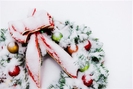 seasonal - Close up of a snowcovered Christmas wreath with a red bow lying in the snow in Fairbanks, Alaska Stock Photo - Rights-Managed, Code: 854-02955843