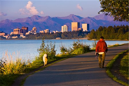 seasonal - People jogging, walking and biking on the Tony Knowles Coastal Trail with Downtown Anchorage skyline in the distance, Anchorage, Southcentral Alaska, Summer Stock Photo - Rights-Managed, Code: 854-03645940