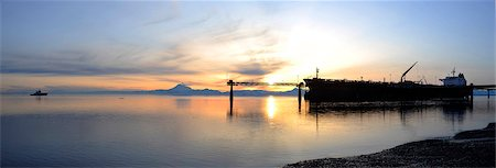 panoramic winter scene - Sunset view of a Russian oil tanker off loading oil at the Kenai Tesoro refinery with Mt. Redoubt venting steam in the background, Kenai Peninsula, Southcentral Alaska, Winter Stock Photo - Rights-Managed, Code: 854-03646328