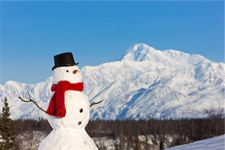 Snowman red scarf and black top hat sitting on a hillside with Mount McKinley in the background, Denali State Park, Southcentral Alaska, Winter Stock Photo - Rights-Managed, Code: 854-03646484
