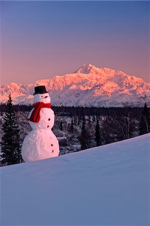Snowman red scarf and black top hat sitting on a hillside with Mount McKinley in the background at sunrise, Denali State Park, Southcentral Alaska, Winter Stock Photo - Rights-Managed, Code: 854-03646482