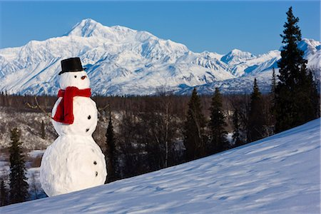 Snowman red scarf and black top hat sitting on a hillside with Mount McKinley in the background, Denali State Park, Southcentral Alaska, Winter Stock Photo - Rights-Managed, Code: 854-03646483