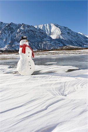 Snowman with a red scarf and black top hat sitting on the frozen Nenana River with the Alaska Range foothills in the background, Southcentral Alaska, Winter Stock Photo - Rights-Managed, Code: 854-03646508