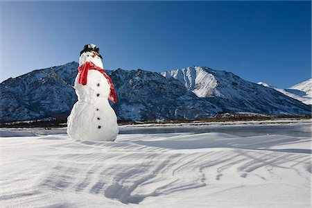 Snowman with a red scarf and black top hat sitting on the frozen Nenana River with the Alaska Range foothills in the background, Southcentral Alaska, Winter Stock Photo - Rights-Managed, Code: 854-03646509