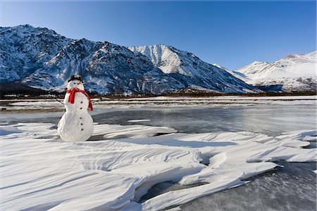 Snowman with a red scarf and black top hat sitting on the frozen Nenana River with the Alaska Range foothills in the background, Southcentral Alaska, Winter Stock Photo - Rights-Managed, Code: 854-03646502