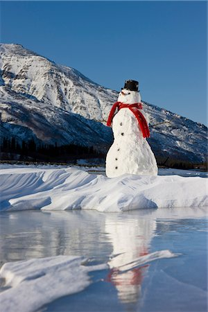 Snowman with a red scarf and black top hat sitting on the frozen Nenana River with the Alaska Range foothills in the background, Southcentral Alaska, Winter Stock Photo - Rights-Managed, Code: 854-03646515