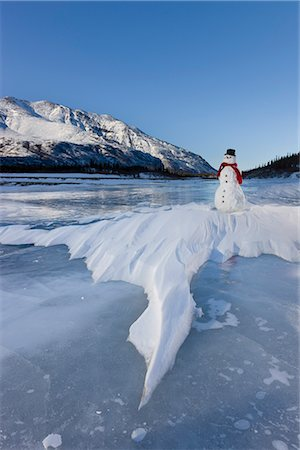Snowman with a red scarf and black top hat sitting on the frozen Nenana River with the Alaska Range foothills in the background, Southcentral Alaska, Winter Stock Photo - Rights-Managed, Code: 854-03646517