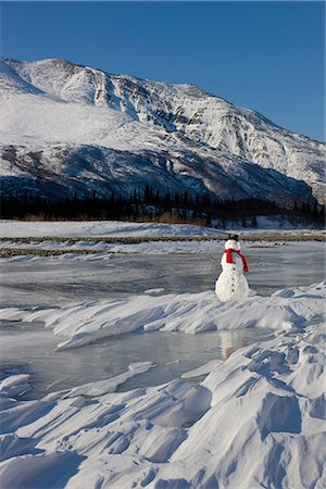 Snowman with a red scarf and black top hat sitting on the frozen Nenana River with the Alaska Range foothills in the background, Southcentral Alaska, Winter Stock Photo - Rights-Managed, Code: 854-03646519
